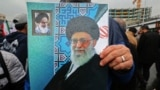 An Iranian holds up a poster showing a portrait of the country's Supreme Leader Ali Khamenei (C) with a small portrait in the corner showing Islamic Revolution founder Ayatollah Ruhollah Khomeini, during a ceremony celebrating the 40th anniversary.