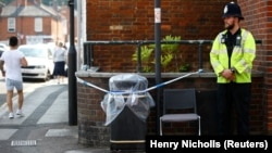 A police officer guards a cordoned off rubbish bin on Rolleston Street in Salisbury, England, on July 5 after it was confirmed that two new people had been poisoned with the nerve agent Novichok.