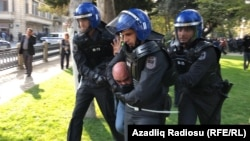 An activist is taken away by police in Baku today.