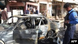 The wreckage of a car at the site of a car bomb Al-Hamdaniya in March