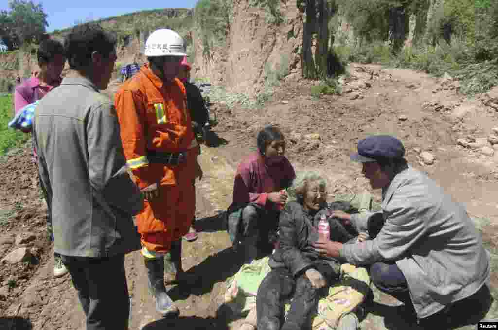 A man offers water to a woman injured in the quake.