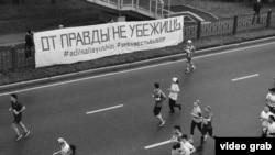 Участники марафона пробегают мимо баннера Тулесовой и Толымбекова, Алматы, 21 апреля 2019 года.