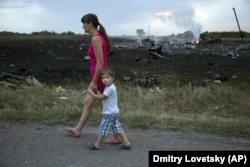 Женщина с ребенком проходит возле одного из мест падения обломков «Боинга», сбитого российской установкой «Бук», в результате чего погибли 298 человек, в том числе 80 детей. Донецкая область, неподалеку села Грабово, 17 июля 2014 года