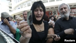 A woman holds a picture of her son, whom she says became an invalid from injuries sustained while in prison, during a protest rally in Tbilisi on September 19.
