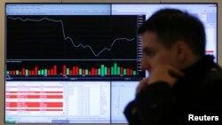 Мужчина проходит мимо экрана фондовой биржи в Москве. 14 марта 2014 года.