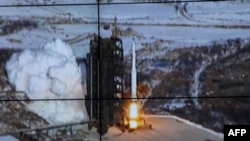 The rocket Unha-3, carrying the satellite Kwangmyongsong-3, is monitored on a large screen at a satellite control center in North Korea on December 12.