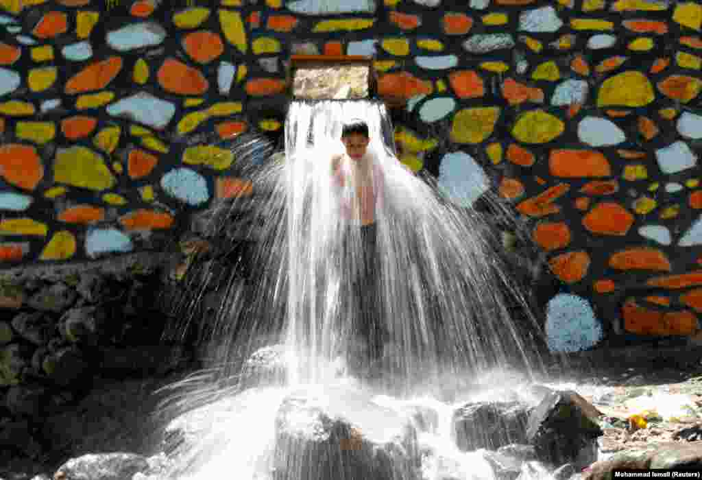 An Afghan boy cools off under a waterfall in Kabul's Paghman district. (Reuters/Mohammad Ismail)