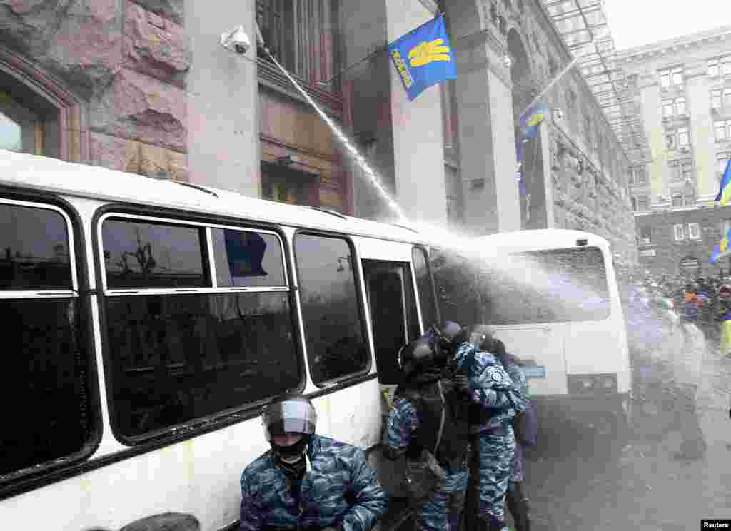 Ukrainian antigovernment protesters spray riot police with a water hose to prevent them from entering the City Hall, which they have occupied in Kyiv, on December 11. (Reuters/Valentin Ogirenko)