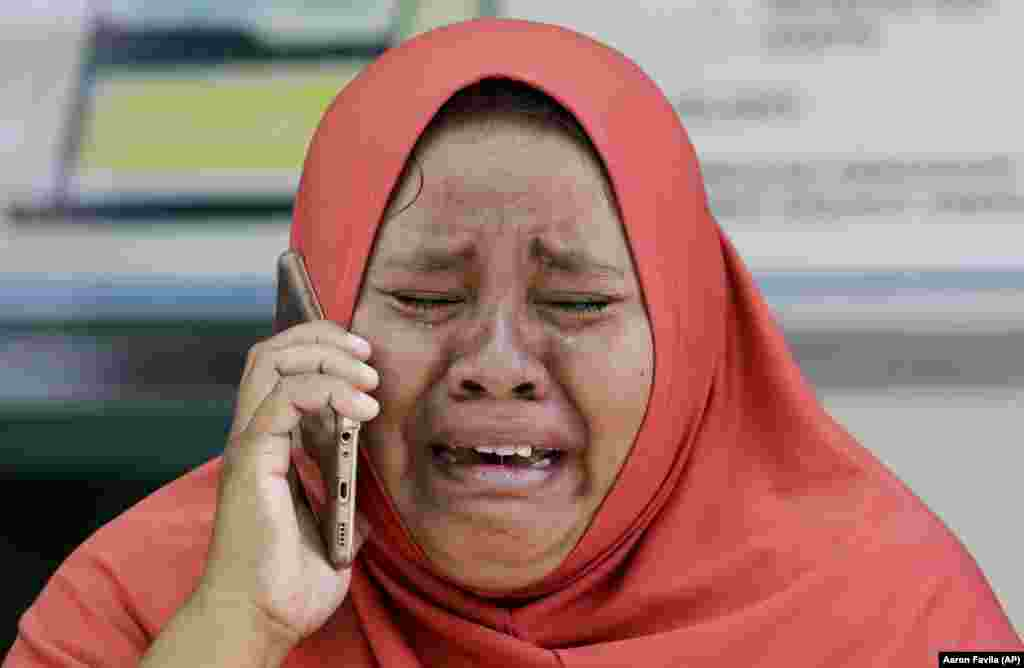 A woman cries as she uses the recovered mobile phone of her daughter, who was killed in the massive earthquake in Palu, Central Sulawesi, Indonesia. The mother did not get the chance to see the body of her daughter before she was buried earlier in a mass grave. (AP/Aaron Favila)
