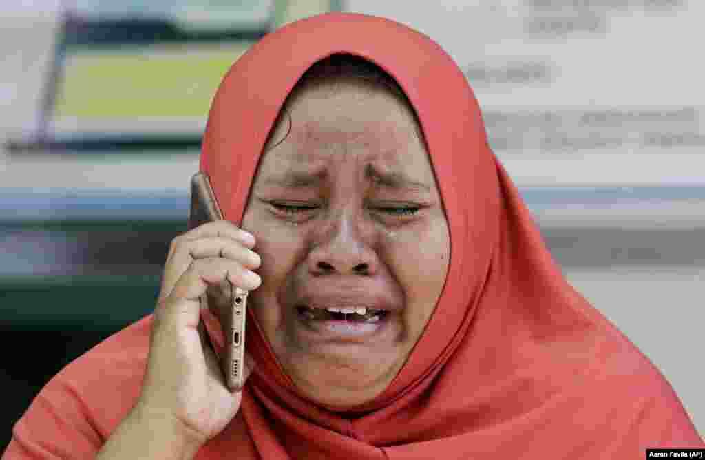 Paluda, Indoneziýanyň Sulawesi adasynda bolan ýer titremesinde ölen gyzynyň harabalykdan tapylan mobil telefonyny eline alyp aglaýan aýal. Ene öz gyzynyň jesedini hem görüp bilmedi, ol biraz öň doganlyk mazarynda jaýlandy. (AP/Aaron Favila)