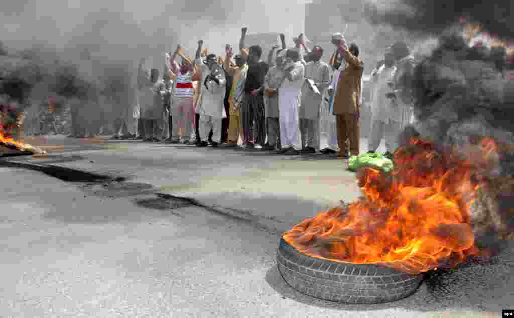 Supporters of Tahir-ul-Qadri, the head of political party Pakistan Awami Tehreek, burn tires as they shout slogans against the killing of party workers in Lahore during a protest in Multan. (EPA/Faisal Karim)