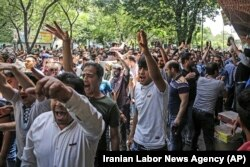 In this June 25, 2018 file photo, a group of protesters chant slogans at the old grand bazaar in Tehran, Iran, as the national currency loses value and inflation picks up.