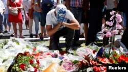 A man reacts near bouquets of flowers as people pay tribute near the scene where a truck ran into a crowd at high speed killing scores and injuring more who were celebrating the Bastille Day national holiday, in Nice, France, July 15, 2016.