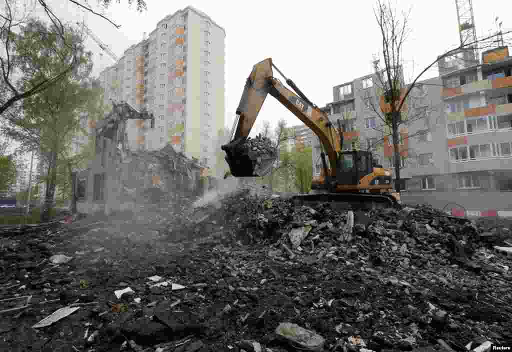 A digger scoops up what remains of a Soviet-era apartment block on May 16.