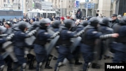 A line of Ukranian riot police moves past protesters in Independence Square in Kyiv.
