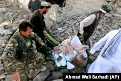 An Afghan security member and people carry an injured man after a suicide attack in Zabul on September 19.