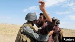 يو افغان پوليس په هلمند کې يو سړی تلاشي کوي.