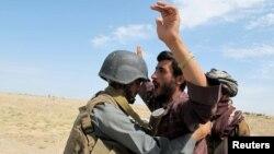 Жергілікті тұрғынды тексеріп жатқан ауғандық полицей, Гильменд уәлаяты. (Көрнекі сурет)