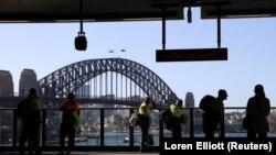 Пассажиры на железнодорожной платформе перед мостом Харбор-Бридж в Сиднее. Сентябрь 2020 года