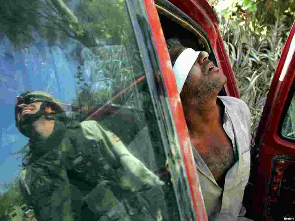 An Iraqi man suspected of having explosives in his car is held after being arrested by the U.S army near Baquba, Iraq, October 15, 2005. Iraqis headed to the polls in an historic referendum on Saturday, with up to 15 million eligible voters deciding on a controversial new post-Saddam Hussein constitution that its backers hope will unite the torn country. Amid intense security, including a ban on all traffic, voters flowed on foot to polling stations across Baghdad. REUTERS/Jorge Silva