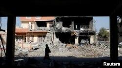 Маж поминува покрај урната куќа во Мосул.