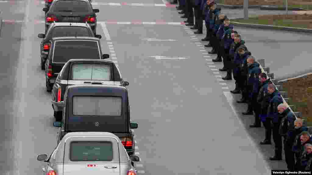 A motorcade of hearses carrying the bodies moves down a road near the airport.