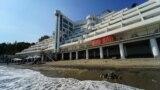 Километровый спуск к поселковым пляжам вдоль расписанного бетонного забора санатория «Айвазовское»