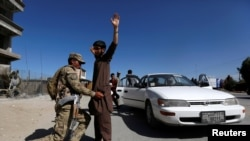An Afghan policeman inspects passengers at a checkpoint on the outskirts of Jalalabad, capital of Nangarhar province on April 29.