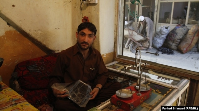 "A Pakistani hashish seller shows off his ""black gold"" in the country's northern tribal region."