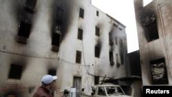 لیبیا:حکومت ضد مظاهرچي د یوې سوځول شوې حکومتي ودانۍ مخې ته ولاړ دی.د۲۰۱۱م کال د فبرورۍ ۲۳ نېټه