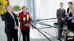 Cancelarul Angela Merkel și directorul FMI Dominique Strauss-Kahn