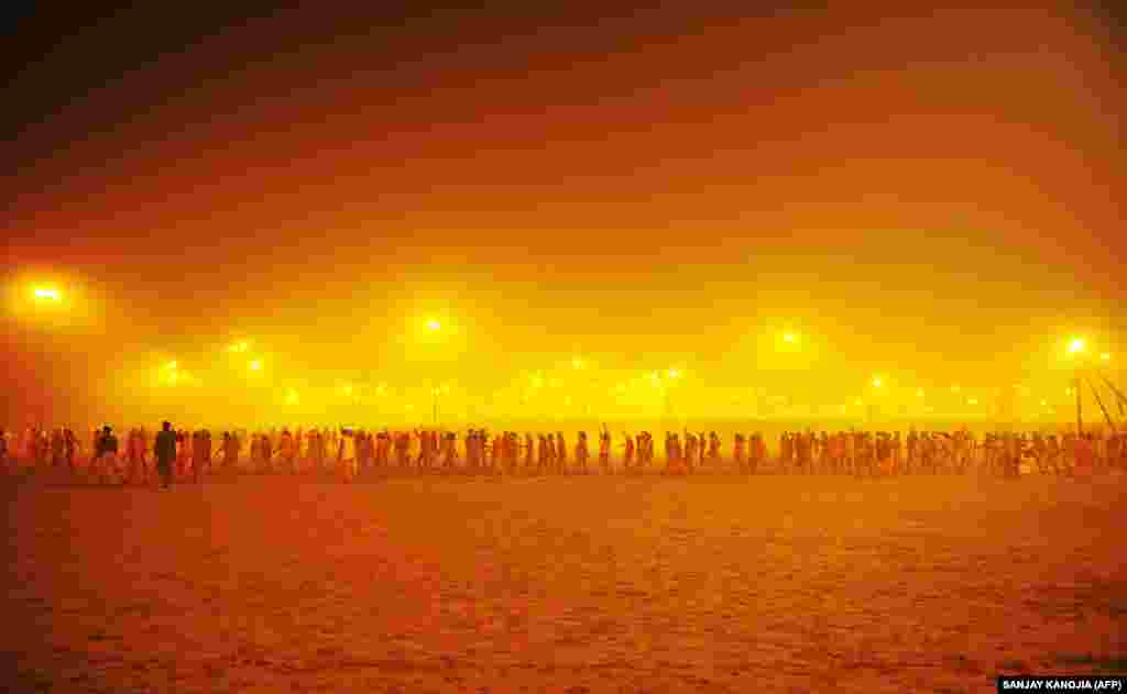 Holy men walk in a procession toward the Sangham, or the confluence of the the Yamuna and Ganges rivers, to bathe before sunrise during the Kumbh Mela in Allahabad, India. The Kumbh Mela in the Indian town of Allahabad will see up to 100 million worshippers gather over the next 55 days to take a ritual bath in the holy waters, believed to cleanse sins and bestow blessings. (AFP/Sanjay Kanojia)