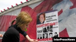 "Demonstrators put up posters calling for the punishment of the ""murderers of Sandro Girgvliani"" at a rally in Tbilisi in April 2006."