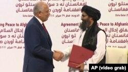 Специальный представитель США по примирению в Афганистане Залмай Халилзад (слева) и лидер талибов мулла Барадар Абдул-Гани на церемонии подписания соглашения об установлении мира в Афганистане, Доха, Катар, 29 февраля, 2020