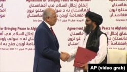 FILE: U.S. Special Representative for Afghanistan Reconciliation Zalmay Khalilzad and Taliban leader Mullah Baradar Abdul-Ghani shaking hands after signing an agreement on February 29.