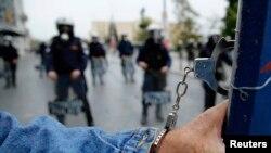 Жаппай ереуілден соң өзін бағанға кісендеп тастаған наразы мен полиция жасағы. Афин, Грекия, 27 қараша 2014 жыл.