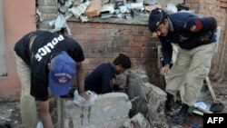 Pakistani police examine the site of a suicide bomb blast in Peshawar.