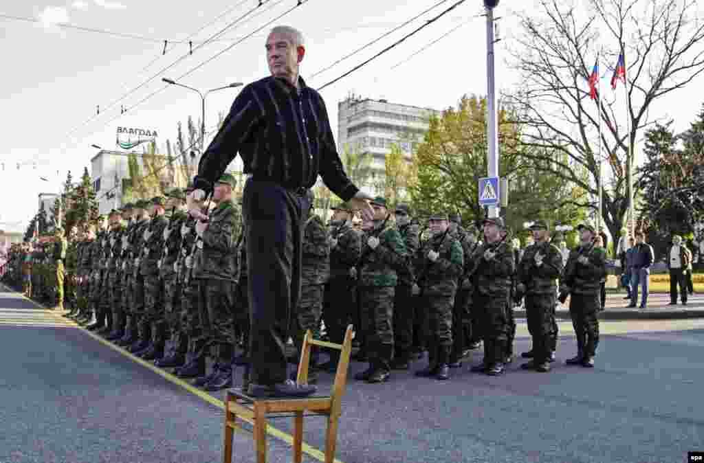 Bir adam oturgyjyň üstünde dur, seperatist pitneçiler Donetsk şäheriniň merkezinde harby parada taýýarlanýar. (epa/Alexander Ermochenko)