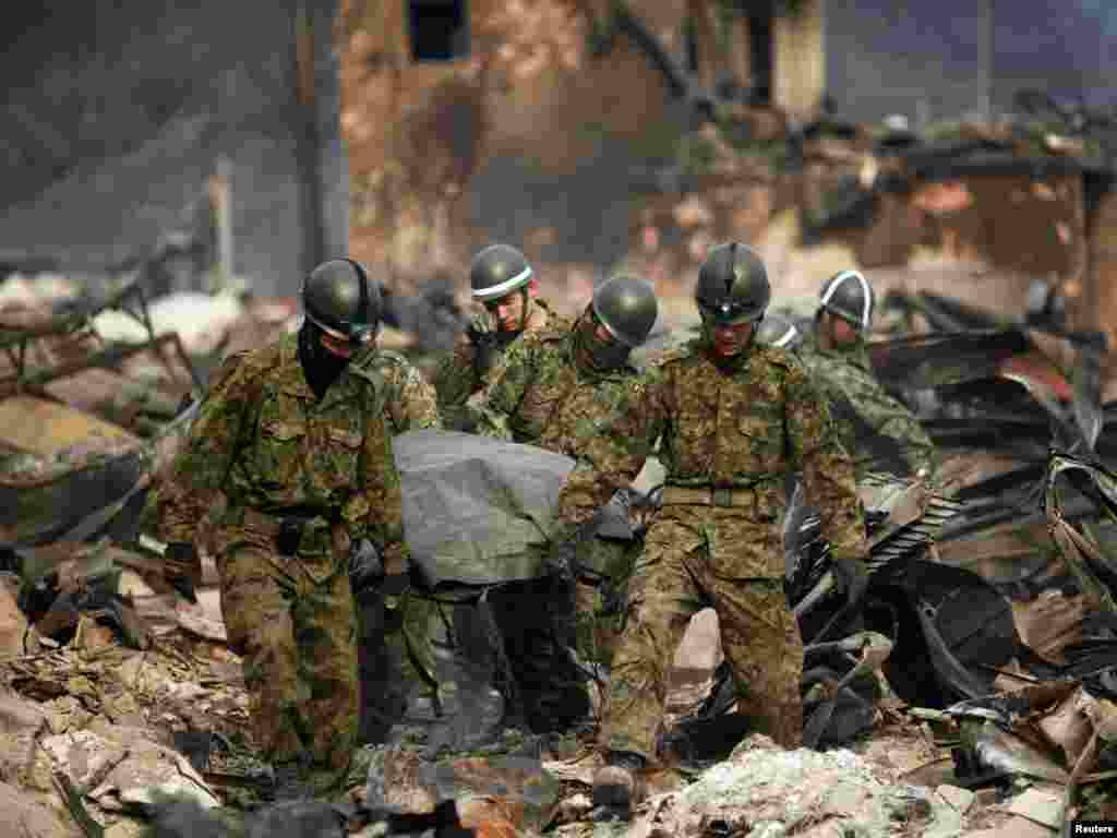 Rescue workers carry the body of a tsunami victim in the town of Otsuchi on March 11