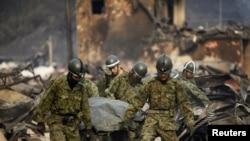 Куткаруучулар цунами каптаган Отсучи шаарчасында урандылар астынан өлүктөрдү сууруп чыгып жатышат, 14-март, 2011