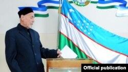 Гражданин Узбекистана бросает бюллетень в урну для голосования. 21 декабря 2014 года.