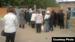 Люди стоят у ворот здания колонии АП-162/4 в городе Павлодаре. 16 сентября 2014 года.