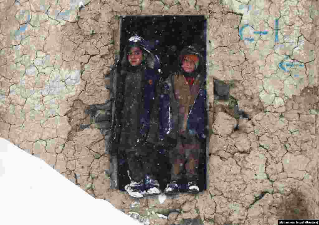 Internally displaced Afghan boys stand outside their shelter during a snowfall in Kabul. (Reuters/Mohammad Ismail)