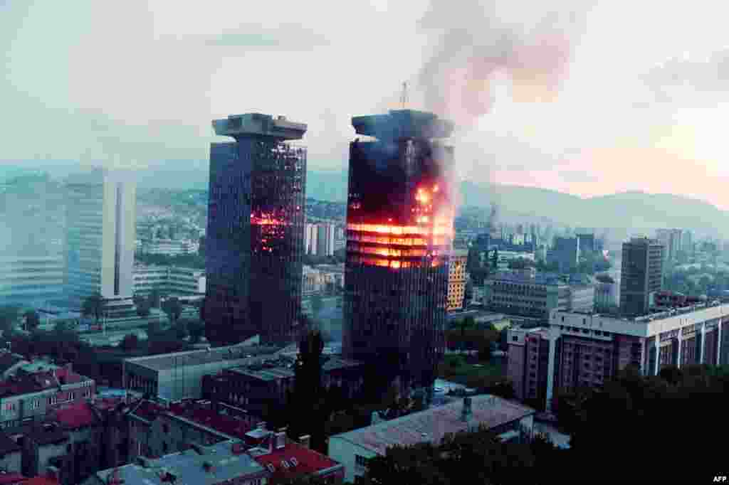 The UNIS twin towers burn along 'Sniper Alley' in downtown Sarajevo as heavy shelling and fighting raged in the Bosnian capital on June 08, 1992.  Nicknamed 'Momo' and 'Uzeir' after a popular ethnic Bosniak and Serb comedy duo, the structures were heavily damaged during the siege of Sarajevo but remained standing to became a symbol of the city's resilience.