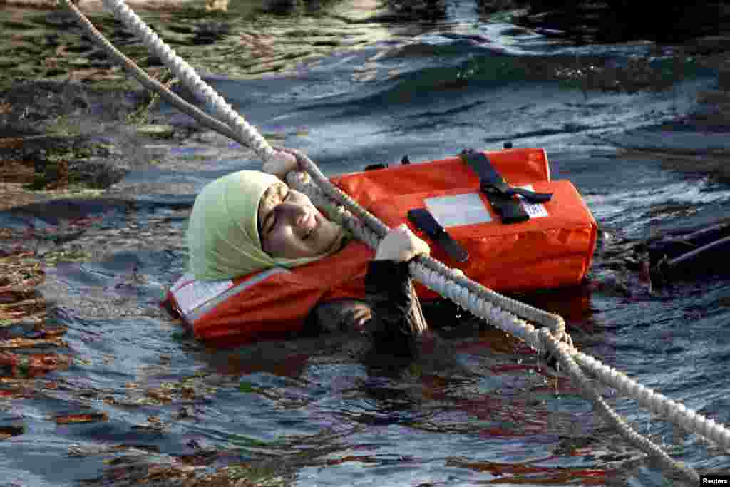 A refugee woman hangs on a rope as a half-sunken catamaran carrying around 150 refugees, most of them Syrians, arrives after crossing part of the Aegean Sea from Turkey, on the Greek island of Lesbos. There were no casualties among the refugees who were traveling on the catamaran, according to a Reuters witness. (Reuters/Giorgos Moutafis)