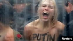 """Активистка FEMEN протестует против визита Путина в Брюссель (надпись на груди девушки: """"Путин – убийца демократии""""), 28 января 2014 года"""