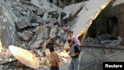 Children walk along a damaged street filled with debris in the Damascus suburb of Zamalka on October 3.