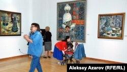 На персональной выставке Гульфайрус Исмаиловой. В кадр попали триптих – «Народная мастерица» (в центре) и натюрморты «Головные уборы» (слева), «Кумыс» (справа). Алматы, 15 мая 2015 года.