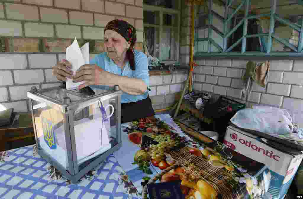 An elderly woman casts her vote at a mobile polling station, outside her home outside Kyiv.