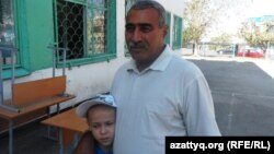 Житель Шымкента Сагынбай Алиев с сыном-второклассником, который учится в школе-лицее № 46. 27 августа 2014 года.